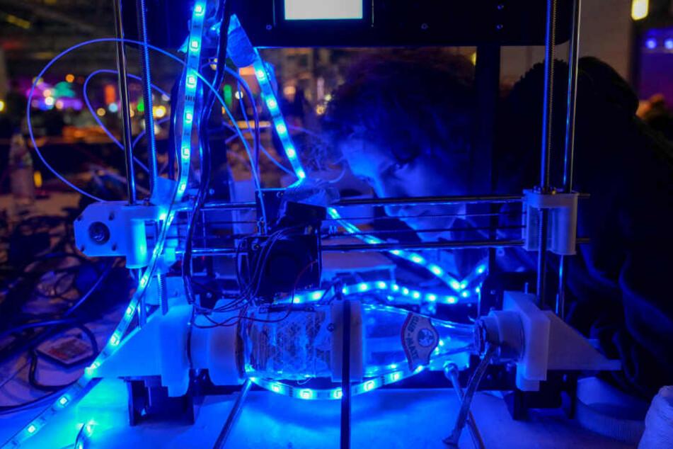 Ein Teilnehmer des CCC 2018 begutachtet seinen 3-D-Drucker, der runde Gegenstände bedrucken kann.