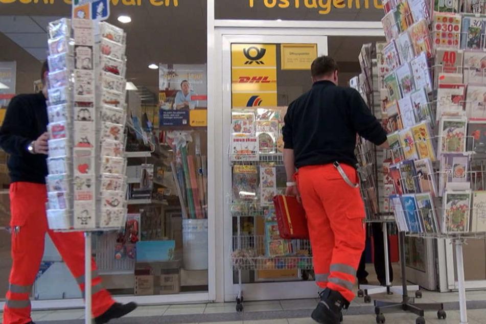 Sanitäter kommen der angegriffenen Postfrau zu Hilfe. Laut Polizei wurde die 43-Jährige leicht verletzt.