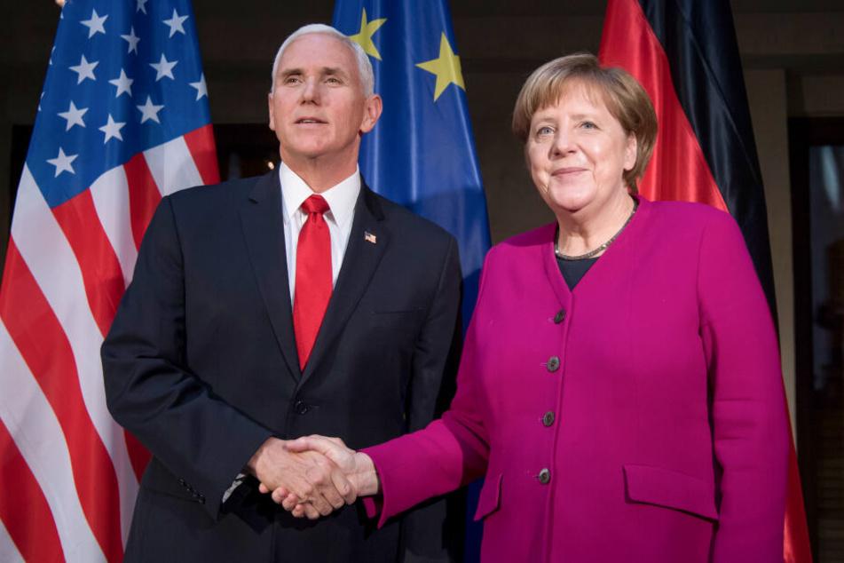 Bundeskanzlerin Angela Merkel (CDU) und Mike Pence, Vizepräsident der USA, begrüßen sich am zweiten Tag der Münchner Sicherheitskonferenz zu Beginn eines Gesprächs.
