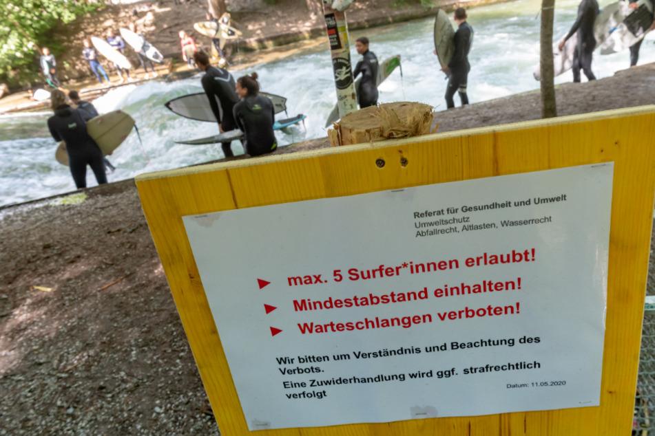 Hinweisschilder hängen vor der Eisbachwelle im Englischen Garten in München.