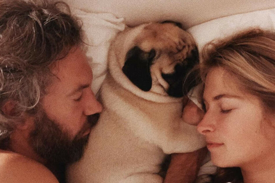 Charlotte, ihr Freund Felix und Mops Mimi liegen gemeinsam im Bett.