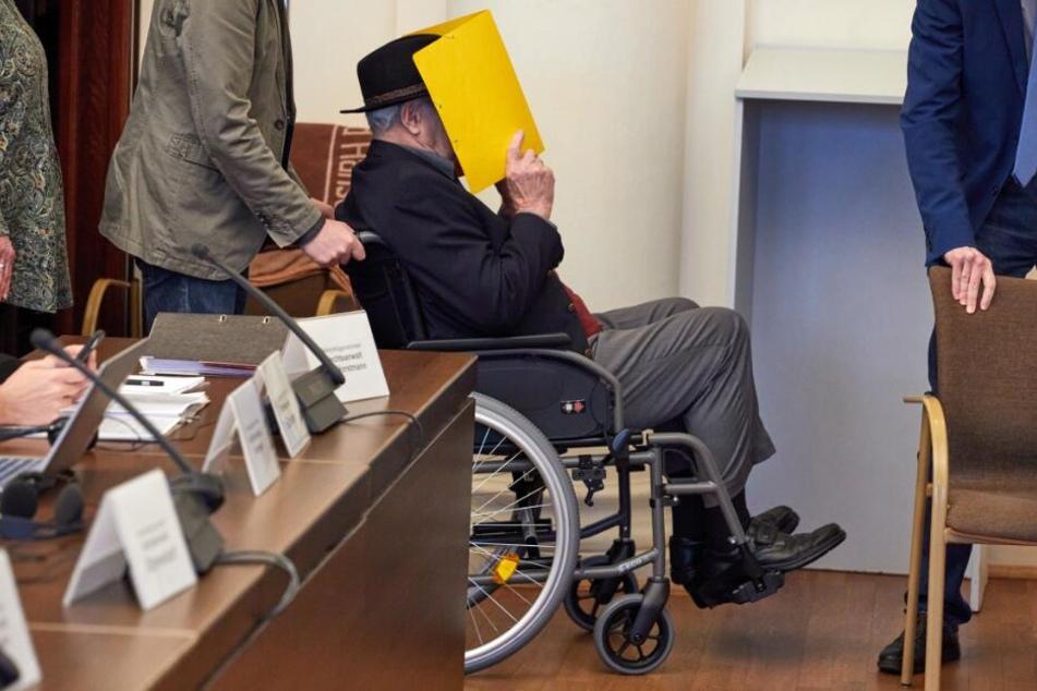 Der Angeklagte wird vor Beginn des Prozesses in einem Rollstuhl in den Gerichtssaal gebracht.