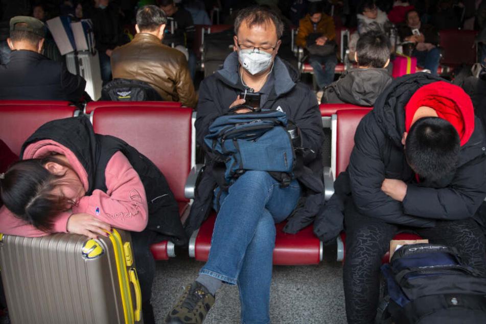 Reisende tragen als Schutzmaßnahme gegen die Verbreitung des Corona-Virus Mundschutz, während sie in einem Wartezimmer am Pekinger Westbahnhof sitzen.