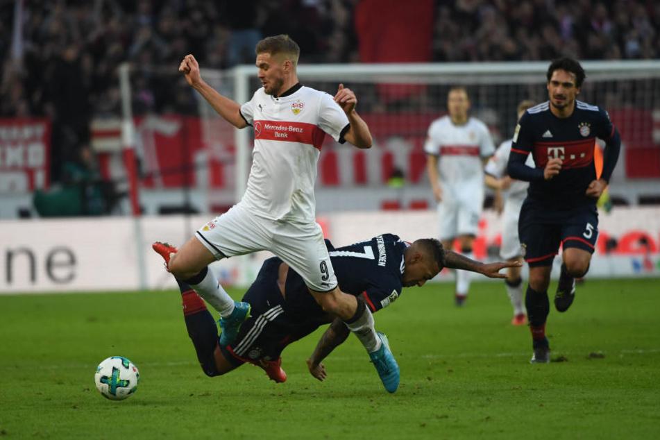 Münchens Jerome Boateng (unten) foult Stuttgarts Simon Terodde (l.)