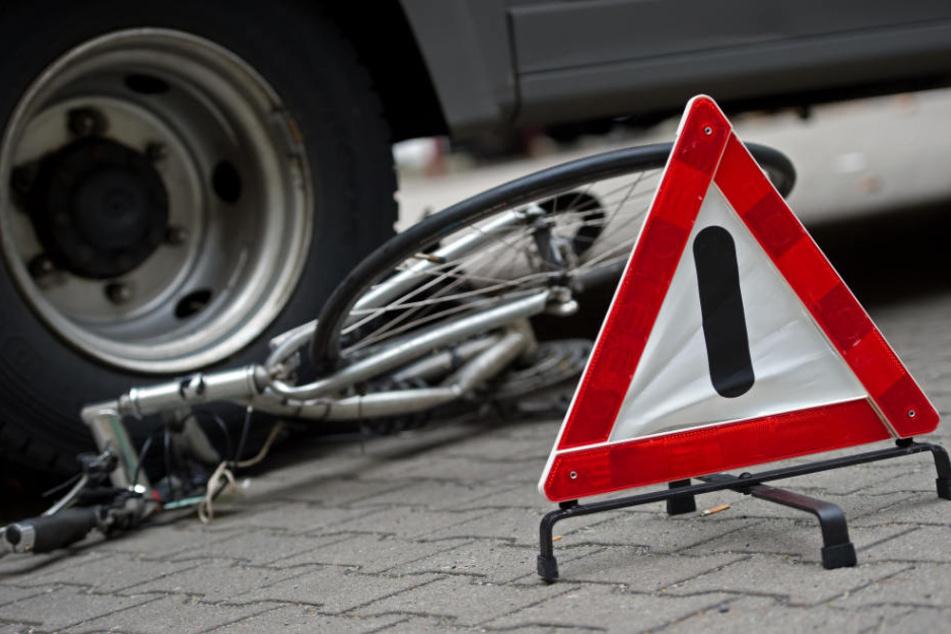 Ein zerstörtes Fahrrad liegt unter den Hinterrädern eines Lkw. (Symbolbild)