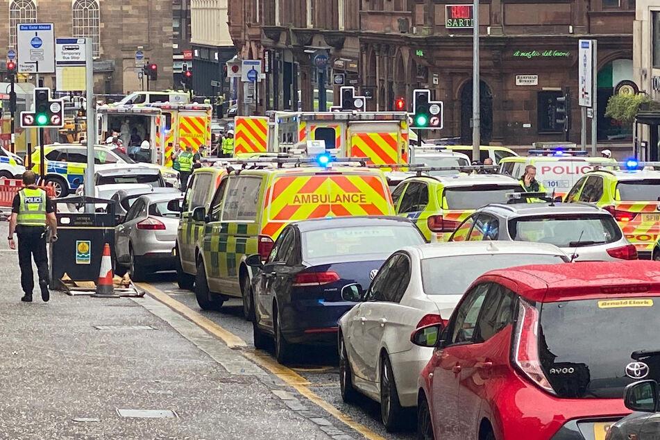 Rettungs- und Polizeifahrzeuge stehen an einem abgesperrten Tatort in der West George Street.