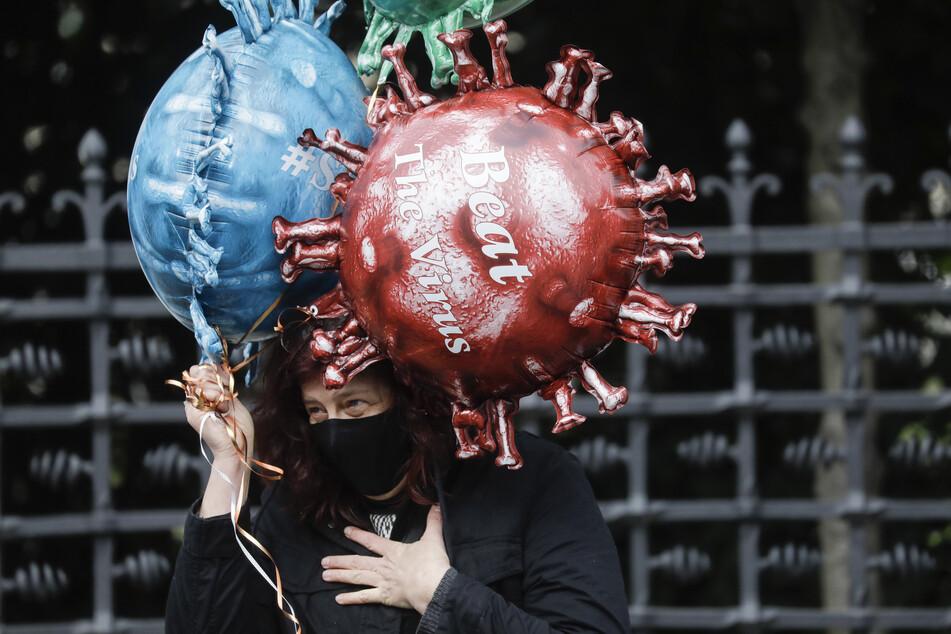 """Brüssel: Eine Frau hält Luftballons in Form eines Virus mit Aufschriften wie """"#staysafe"""" (""""Passt auf euch auf"""") und """"Beat The Virus"""" (""""Bekämpft den Virus"""") vor einem Gebäude, in dem sich ein Beratungsausschuss aus Ministern der belgischen Bundesregierung, der Regionalregierungen und der Gemeinderegierungen trifft."""