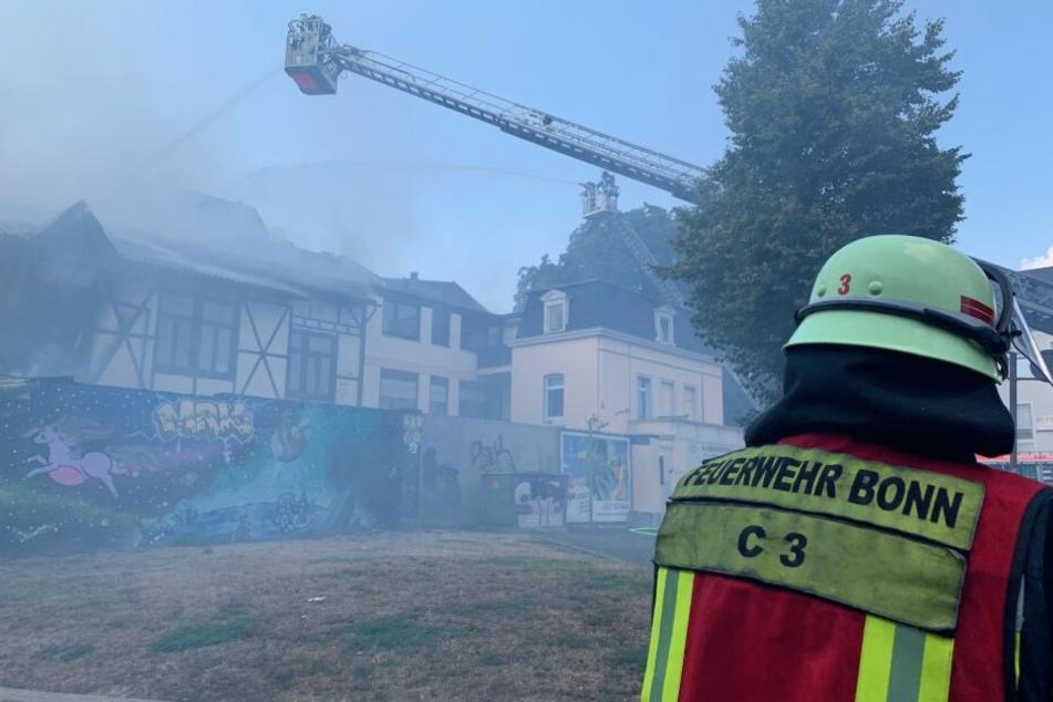 03. August 2019, Nordrhein-Westfalen, Bad Godesberg: Über eine Drehleiter bekämpft die Feuerwehr Bonn den Brand in einer Schreinerei und einem Wohnhaus.