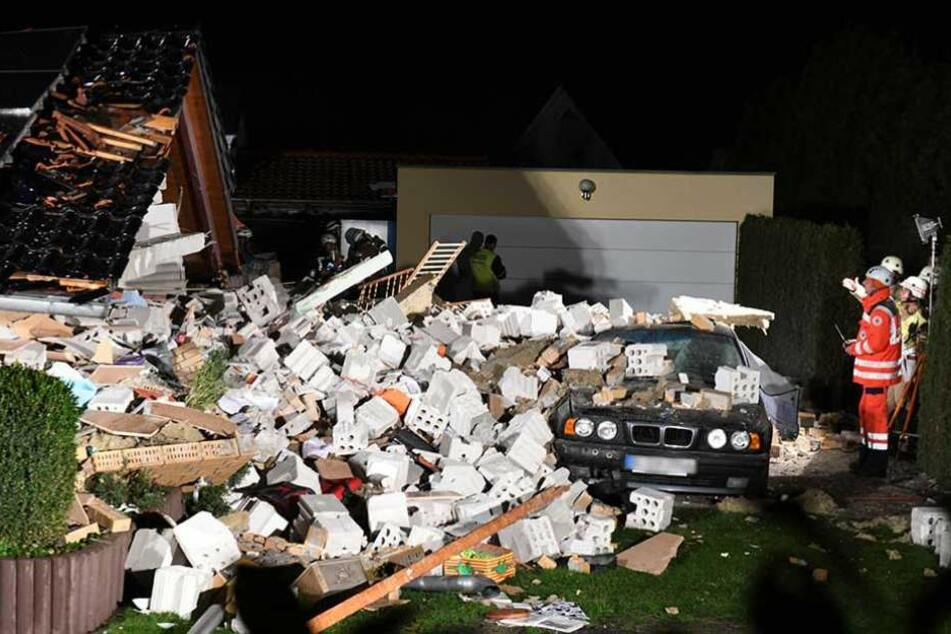 Rettungskräfte untersuchen die Trümmer des eingestürzten Hauses.