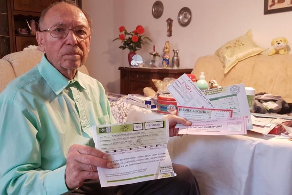 Dieter S. (83) mit der Vielzahl an Gewinnversprechen, die er per Post zugeschickt bekommen hat.
