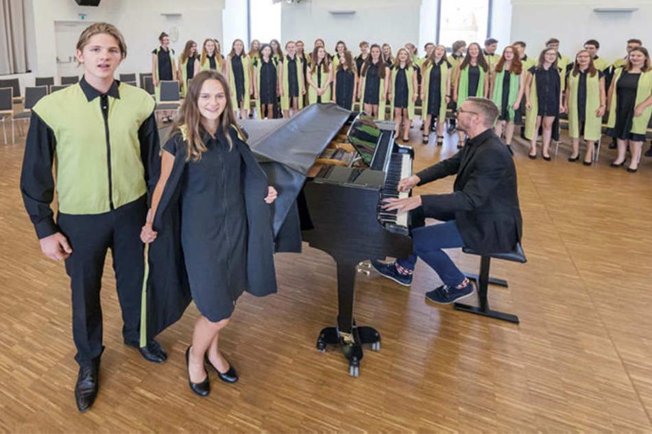 Jenni Marie Wojnowski (15) und Jean Pascal Heinze in der alten unmodernen Chorkleidung, am Flügel Chorleiter Simon Voigtländer (31).
