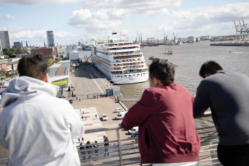 """Drei Männer schauen auf das Kreuzfahrtschiff """"Aida Sol"""" am Cruise Center Altona."""