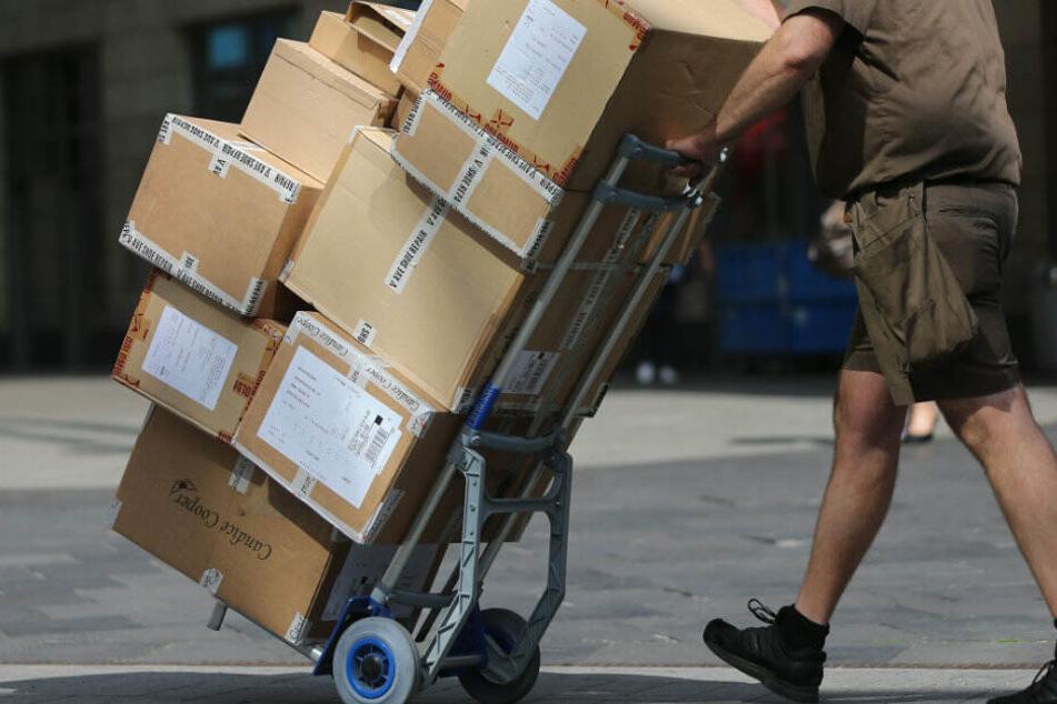 Ein Paketbote liefert Pakete aus. (Symbolbild)