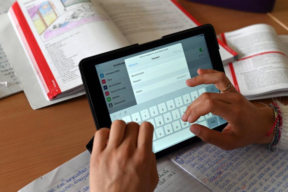 Realschüler einer zehnten Klasse arbeiten in einer Unterrichtsstunde mit Tablets.