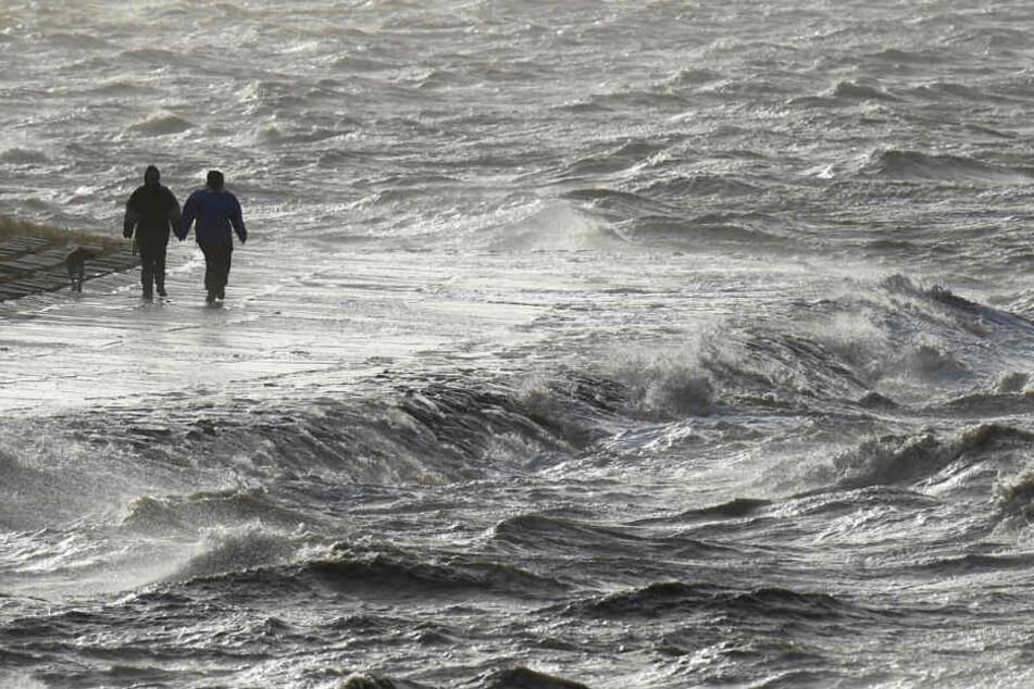 Wellen der aufgepeitschten Nordsee schlagen gegen einen Deich. Zwei Spaziergänger stört das nicht. (Archivbild)