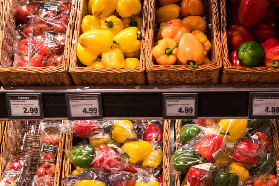 Obst und Gemüse liegen unverpackt oder in Plastik eingehüllt in den Fächern.