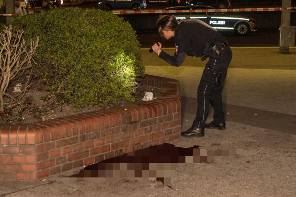 Eine Polizistin sucht mit einer Taschenlampe ein Gebüsch nach Spuren ab.