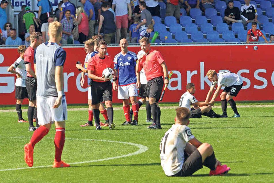 Nach dem Abpfiff hocken die Zwickauer Spieler enttäuscht auf dem Rasen.