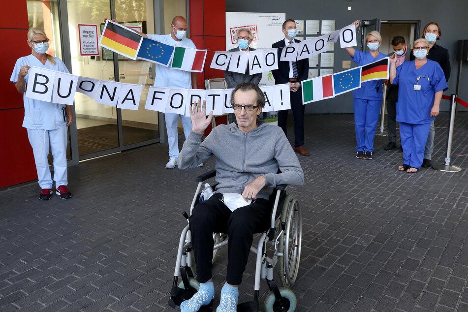 """Der Italiener Paolo Bonacina (56) (M), der letzte aus Italien aufgenommene Covid-19 Patient des St. Josef-Hospitals, wird vom Klinikpersonal mit einem Transparent """"Ciao Pauolo - Buona Fortuna"""" verabschiedet."""