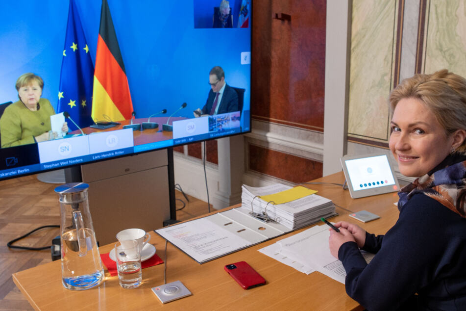 Schwerin: Manuela Schwesig (SPD), die Ministerpräsidentin von Mecklenburg-Vorpommern, sitzt in der Staatskanzlei bei der Video-Schaltkonferenz zur Entwicklung der Corona-Pandemie vor einem Monitor, auf dem Bundeskanzlerin Angela Merkel (CDU) und Michael Müller (SPD), der Regierende Bürgermeister von Berlin, zu sehen sind.