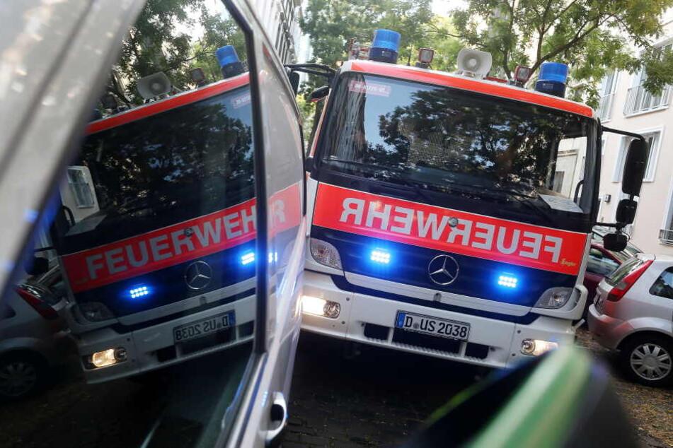 Ein durch einen Falschparker blockiertes Feuerwehrauto mit Blaulicht spiegelt sich in den Scheiben des Falschparkers