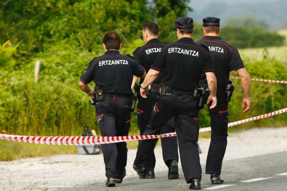 Beamte der baskischen Autonomiepolizei Ertzaintza klettern im Gemeindegebiet Asparrena über eine Absperrung. Sie fanden die Frauenleiche am Donnerstag unweit einer Tankstelle.