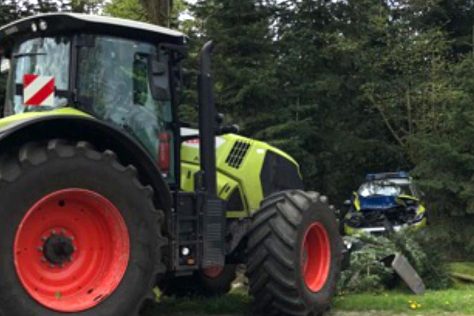 Der Traktor schob den Streifenwagen ins Gebüsch.