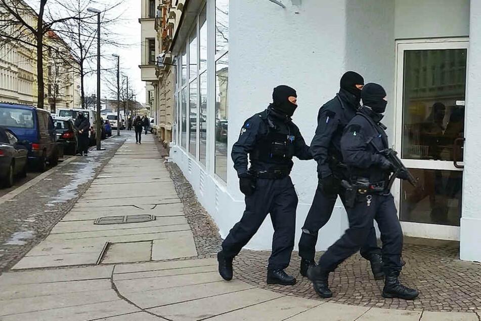 Vermummte Polizisten patroullieren auf der Eisenbahnstraße - zur Absicherung einer Razzia.