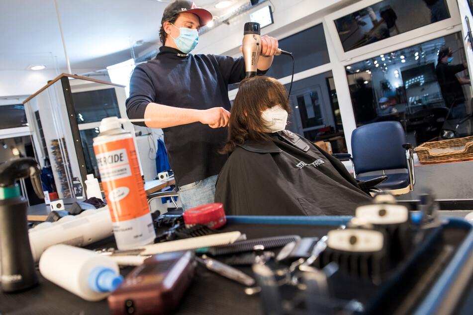 Henry Riehl, Friseur, föhnt einer seiner ersten Kunden nach der Wiedereröffnung, kurz nach Mitternacht die Haare.
