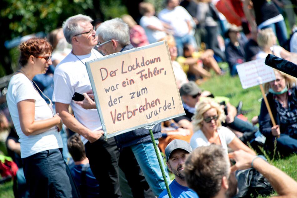 """Teilnehmer halten bei einer Demonstration gegen die Corona-Maßnahmen auf dem Waterlooplatz in Hannover ein Schild mit der Aufschrift """"Der Lockdown war ein Fehler, der zum Verbrechen wurde!""""."""