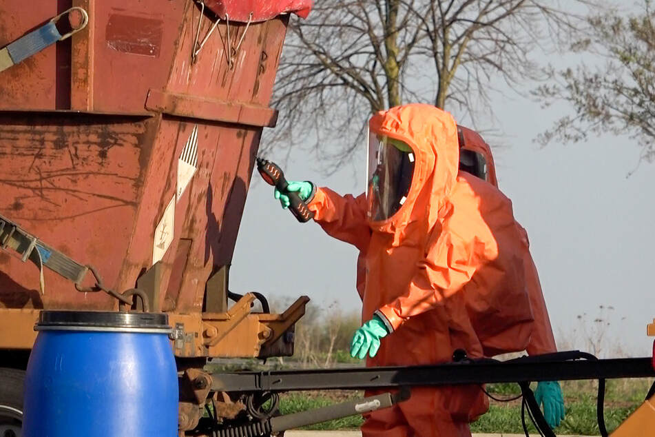 In Chemikalien-Ganzkörperanzügen kümmerten sich Kameraden um die ausgelaufene Flüssigkeit und den leckgeschlagenen Container.