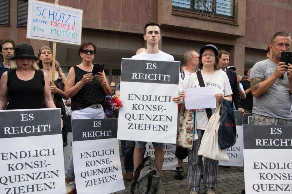 Teilnehmer an einer von der AfD organisierten Mahnwache für die getötete Susanna halten Schilder in die Höhe.