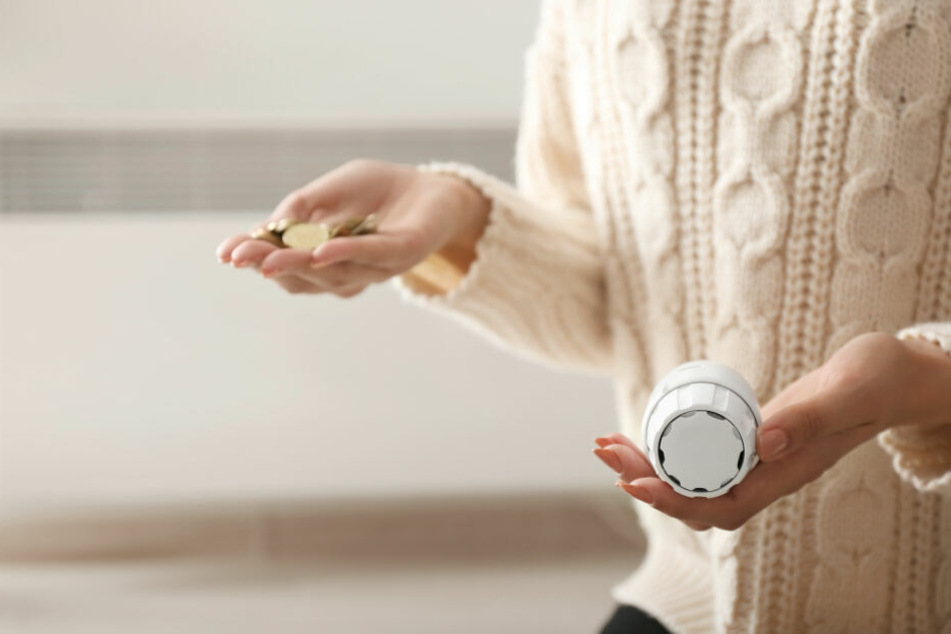 Eine Frau hält ein Heizungsthermostat in der Hand.
