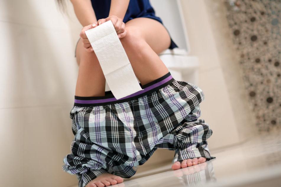 Eine Frau sitzt auf der Toilette. So geht es aktuell vielen Menschen in Australien, die sich mit Kryptosoridiose angesteckt haben.