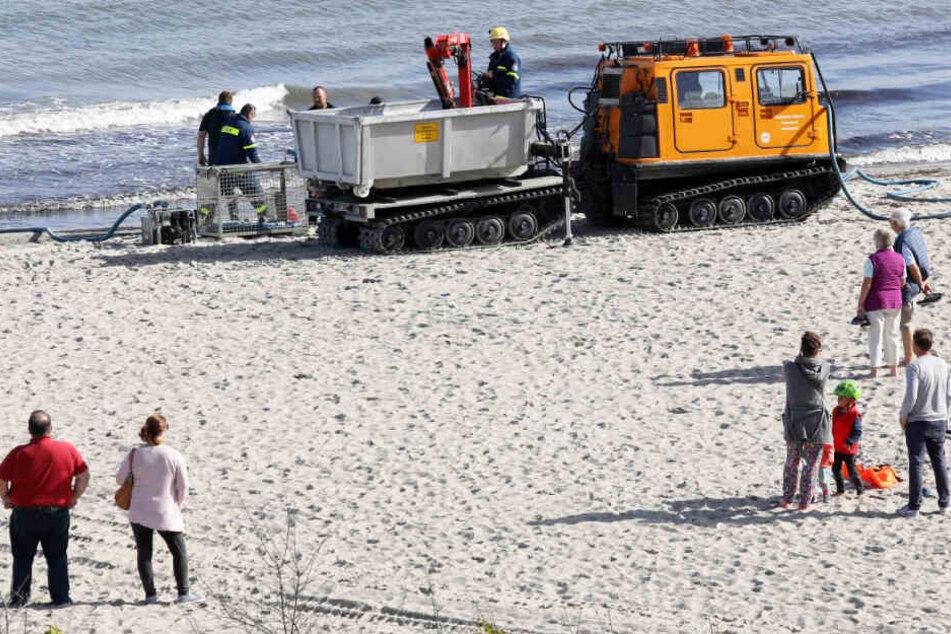 Spaziergänger gucken zu, wie die Helfer mit einem Spezialfahrzeug Geräte zur Aufnahme von angespültem Öl aufbauen.
