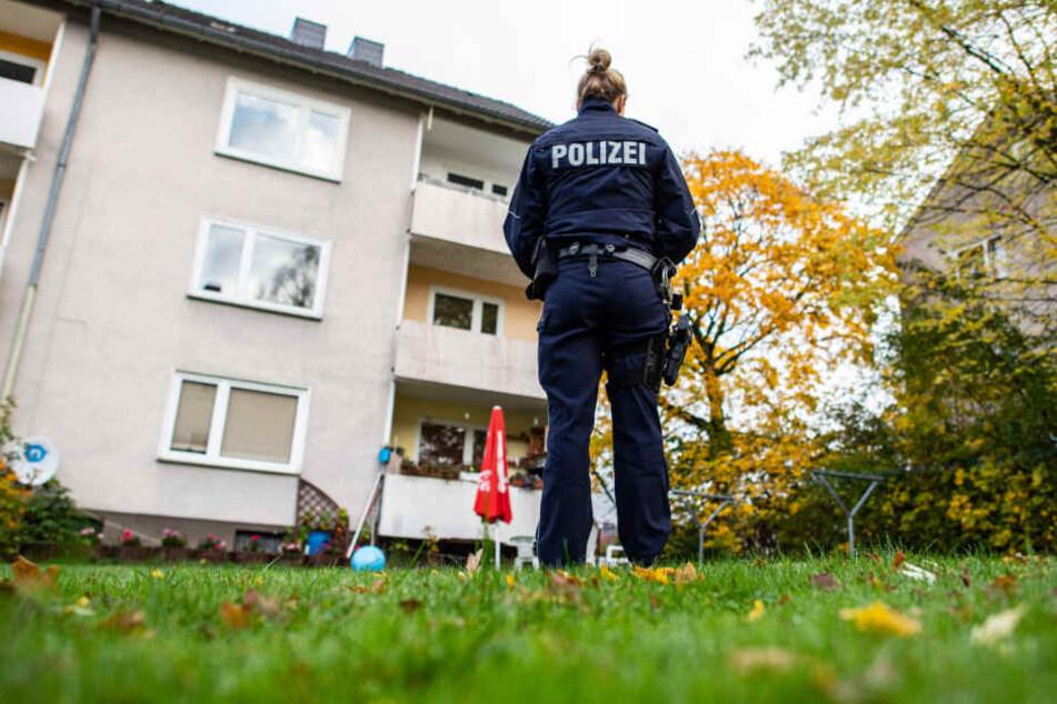 Im Garten des Abwesens steht eine Polizeibeamtin.