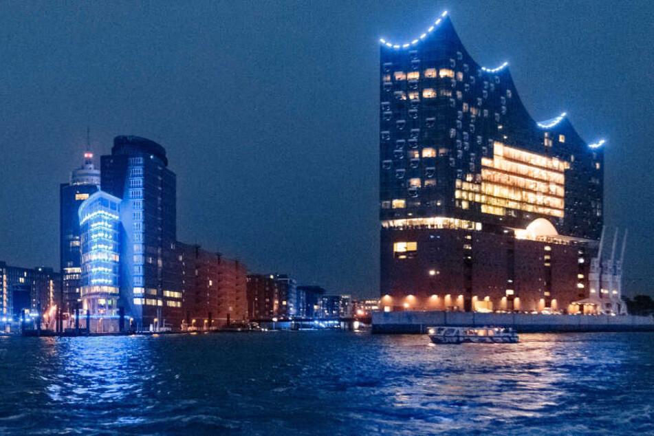 """Die Kehrwiederspitze und die Elbphilharmonie erstrahlen in blauem Licht der Installation """"Blue Port""""."""