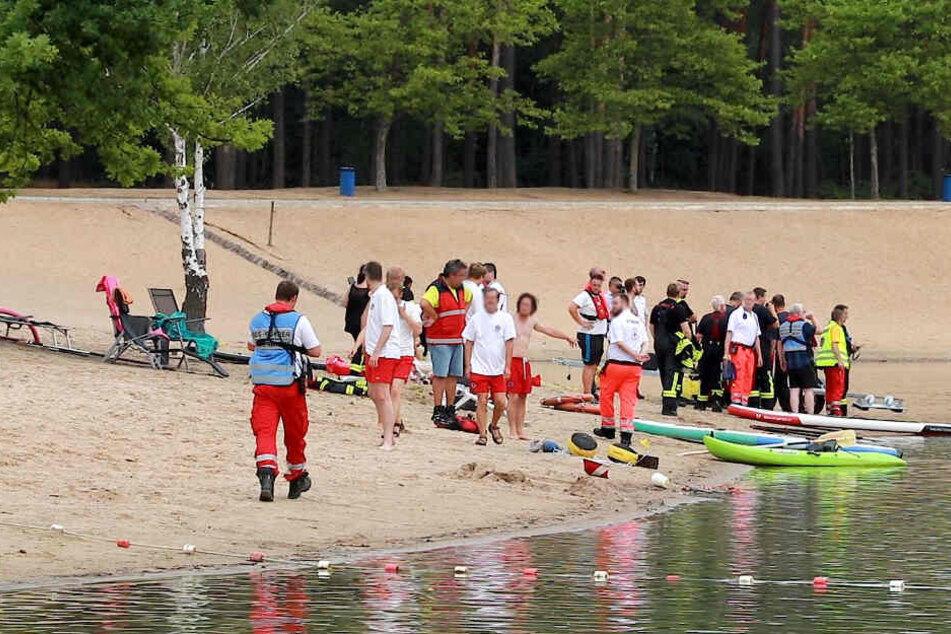 Rettungskräfte stehen am Ufer des Badesees.