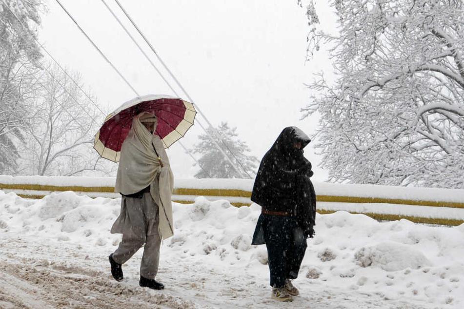 Menschen gehen auf einer schneebedeckten Straße entlang.