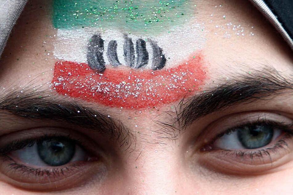 """Eine Frau mit der iranischen Nationalflagge auf der Stirn, aufgenommen am 11.02.2011 in Teheran. Die Polizei im streng islamischen Iran will Frauen, die sich auf den Straßen """"unislamisch"""" kleiden oder benehmen, belehren statt bestrafen."""