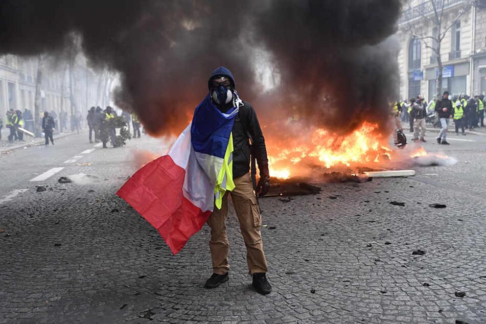 """Ein Protestant der """"Gelben Westen"""" steht im achten Arrondissement mit einer französischen Fahne vor einem brennenden Auto."""