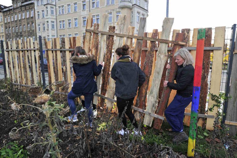 Gemensam mit Kindern eines Jugendclubs baut Pötzsch (r.) einen Zaun am Garten auf.