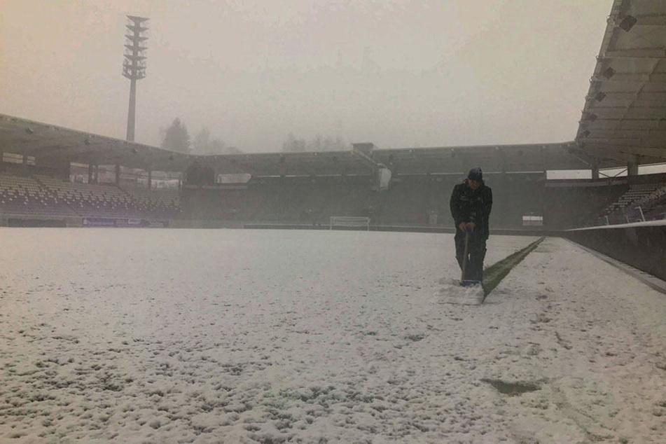 Ein Stadionarbeiter beräumt mit dem Schneeschieber die Außenlinie - ein aussichtsloser Kampf.