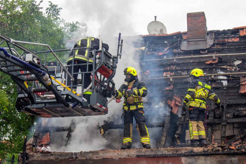 Mit Atemschutzmasken bekämpft die Feuerwehr die Glutnester.