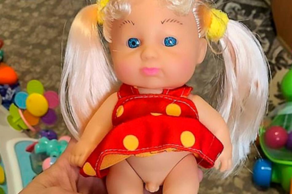 Die Puppe versteckt unter ihrem gepunkteten Kleid einen kleinen Penis.