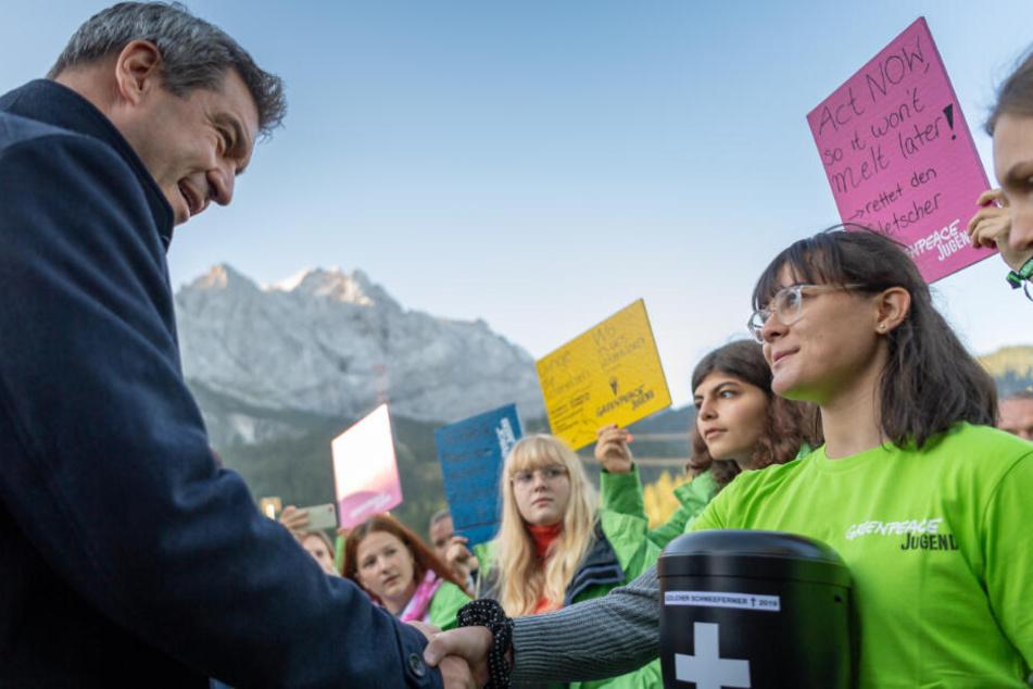 Markus Söder unterhält sich vor Beginn seiner Klimatour in der Zugspitzregion mit jugendlichen Greenpeace Aktivisten.