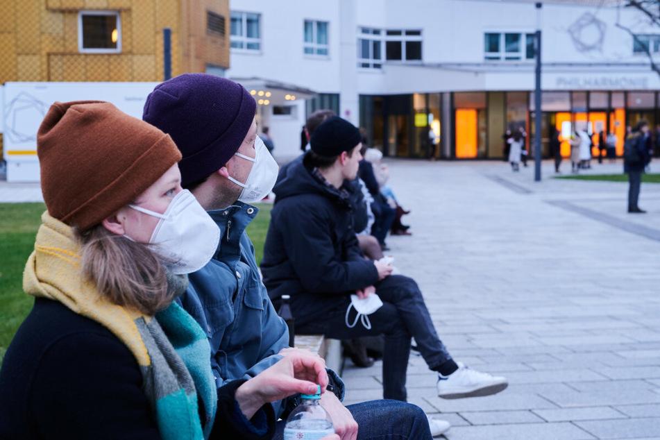 Besucher mit FFP2-Masken sitzen vor der Berliner Philharmonie und warten noch auf die Ergebnisse ihrer Tests auf das Coronavirus