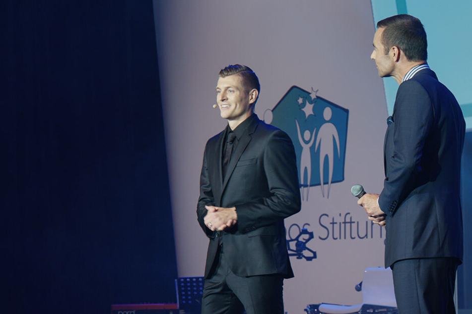 Toni Kroos (l.) hält bei einer Gala seiner Stiftung eine Rede.