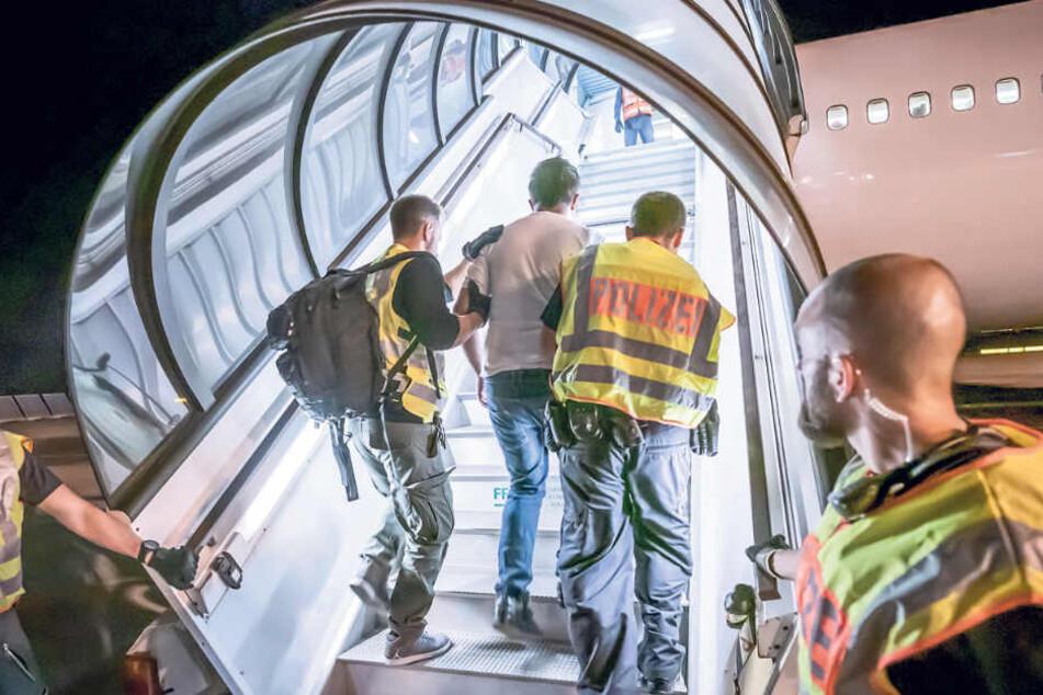 Polizeibeamte führen einen Afghanen die Gangway zum Charterflugzeug hinauf.