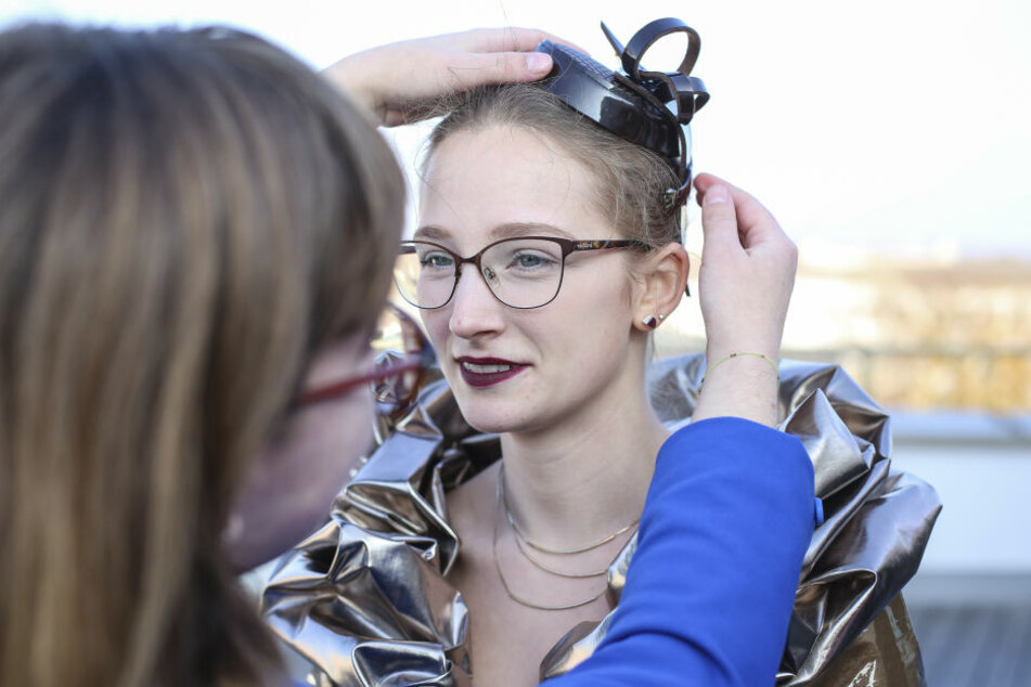 Design-Studentin Nadine Riemer (19, l.) steckt Schoko-Girl Michelle ein Hütchen ins Haar.